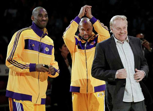 FILE - In this Oct. 26, 2010 file photo, Los Angeles Laker owner Jerry Buss, right, walks out onto the court during the NBA championship ring ceremony as Kobe Bryant, left, and Derek Fisher look on before a basketball game against the Houston Rockets in Los Angeles. Buss, the Lakers' playboy owner who shepherded the NBA franchise to 10 championships, has died. He was 80. Bob Steiner, an assistant to Buss, confirmed Monday, Feb. 18, 2013  that Buss had died in Los Angeles. Further details were not available.(AP Photo/Chris Carlson, File) Photo: Chris Carlson, Associated Press / AP
