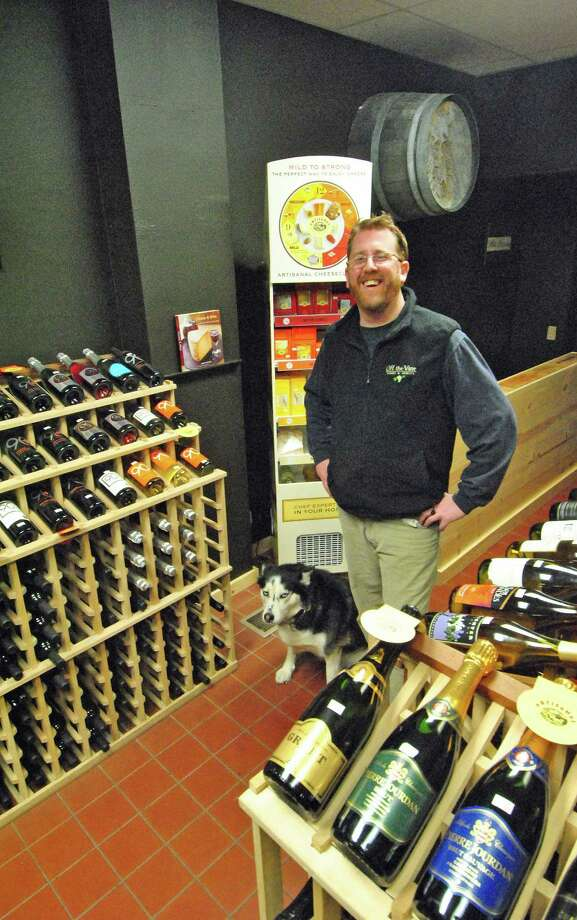 John Noakes and his dog Nikita are enjoying the new location of Off the Vine Wines & Spirits at  67 ½ Winfield St. in East Norwalk. Behind them is a cooler full of cheese that Noakes is now selling at the shop. Photo: Jordan Osterhout/For The Norwalk