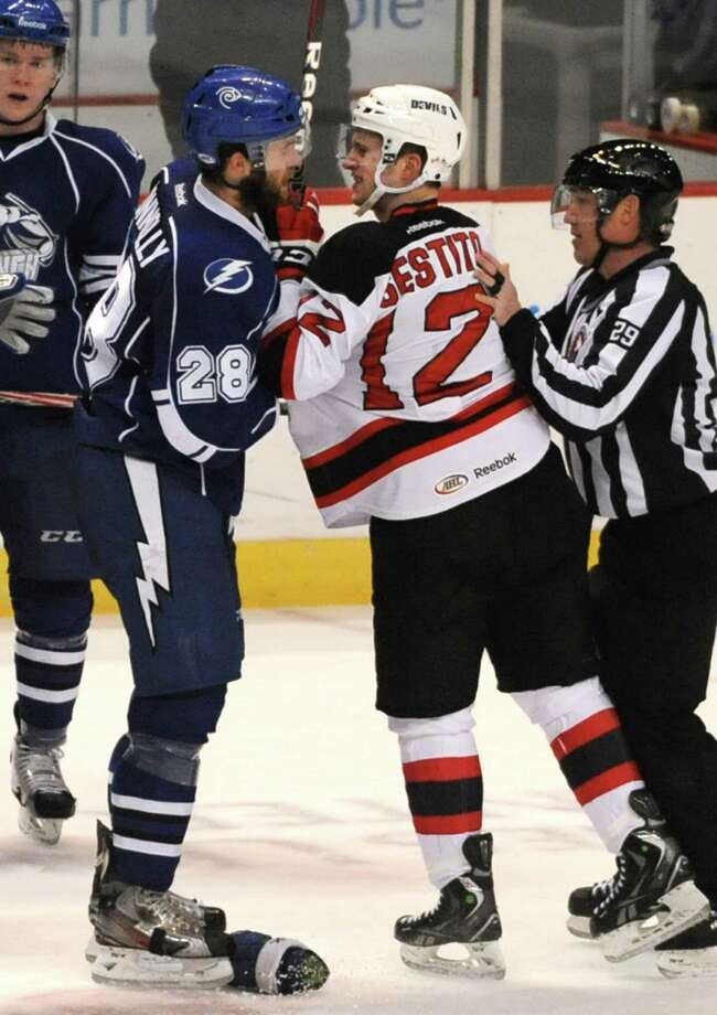Brett Connelly of Syracuse, left, and Tim Sestito of the Albany Devils both get some penalty box time for this scuffle during a hockey game at the Times Union Center on Monday Feb. 18, 2013 in Albany, N.Y.  (Lori Van Buren / Times Union) Photo: Lori Van Buren