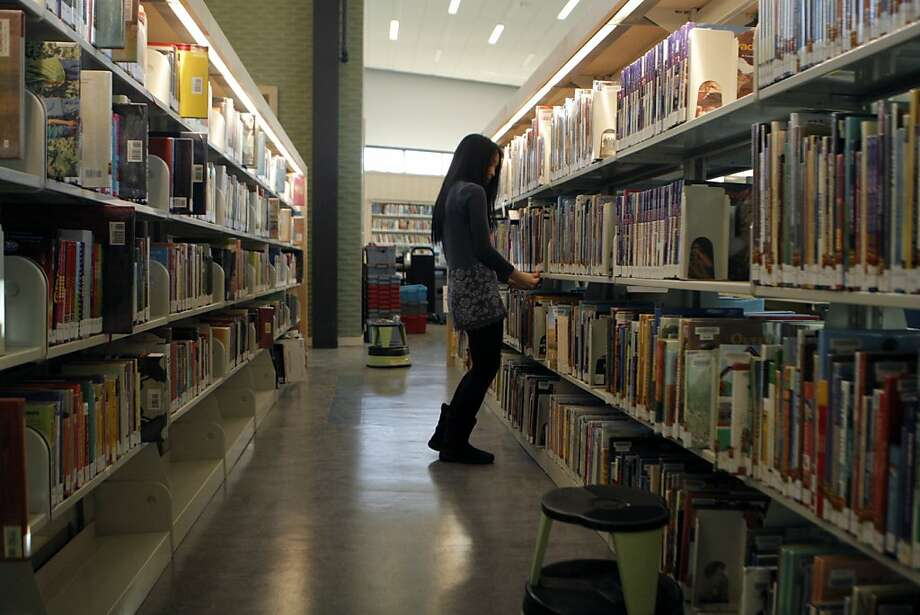 Jennifer Wu straightens up the shelves last week at the Bayview branch library, which opens Saturday. Photo: Jessica Olthof, The Chronicle