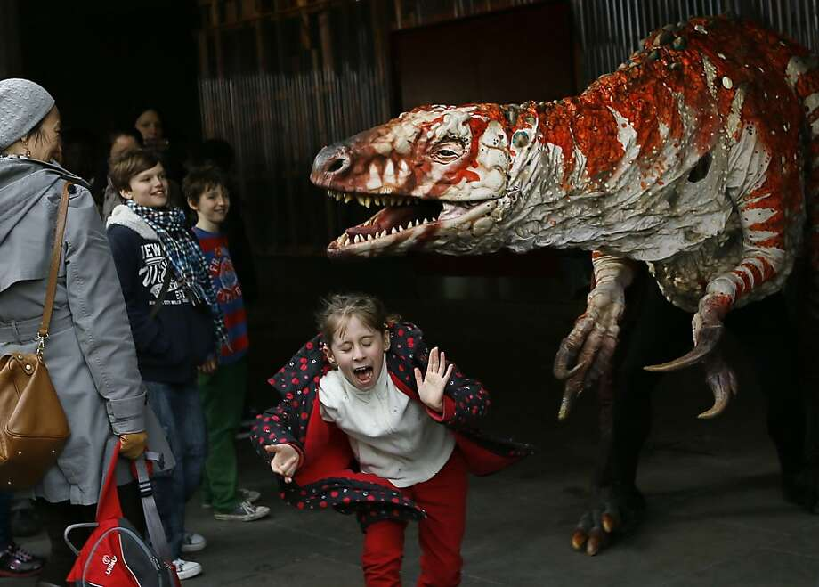 Children react as a carnivorous theropod known as the Australovenator dinosaur walks through crowds along the Southbank, in London, Monday, Feb. 18, 2013. The dinosaur is one of many that can be visited at the Erth's Dinosaur Petting Zoo, visiting from Australia, the creatures can be touched and fed at the Southbank Centre. (AP Photo/Kirsty Wigglesworth) Photo: Kirsty Wigglesworth, Associated Press
