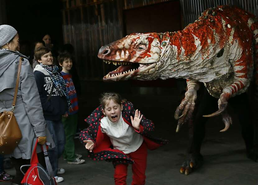 Children react as a carnivorous theropod known as the Australovenator dinosaur walks through crowds