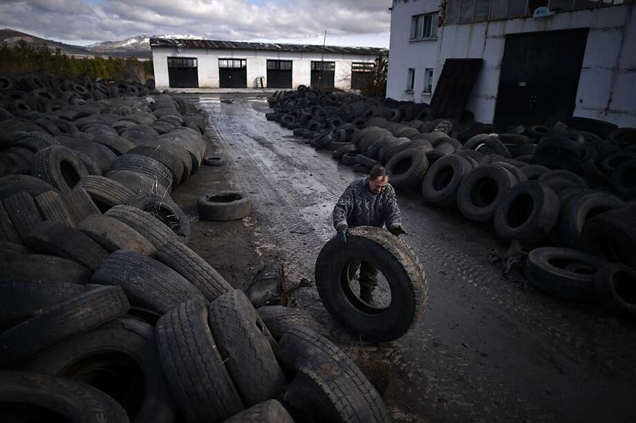 A worker wheels a used tyre for recycling in a factory in the village of Gaber, western Bulgaria, on February 15, 2013. DIMITAR DILKOFF/AFP/Getty Images Photo: Dimitar Dilkoff, AFP/Getty Images