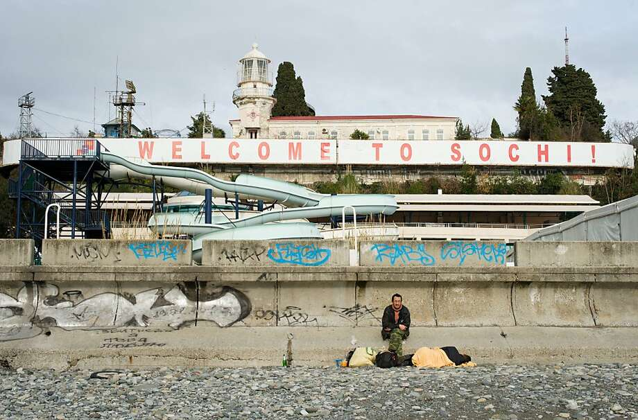 "A man sits among his belongings on the beachfront beneath a large ""Welcome to Sochi!"" sign in central Sochi on February 18, 2013. With a year to go until the Sochi 2014 Winter Games, construction work and development continues as Olympic tests events and World Championship competitions are underway. LEON NEAL/AFP/Getty Images Photo: Leon Neal, AFP/Getty Images"