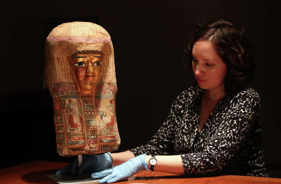 Houston Museum of Natural Science employee Eydie Roja examines a 2,000 plus-year-old mask that is a new acquisition for the Egyptian gallery. Photo: Mayra Beltran, Staff / © 2013 Houston Chronicle