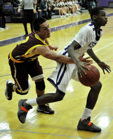 St. Joseph's Jake Pelletier attempts to reach in and steal the ball from Westhill's Jeremiah Livingston during their game at Westhill High School in Stamford on Monday, Feb. 18, 2013. St. Joseph won, 63-61. Photo: Jason Rearick / The News-Times