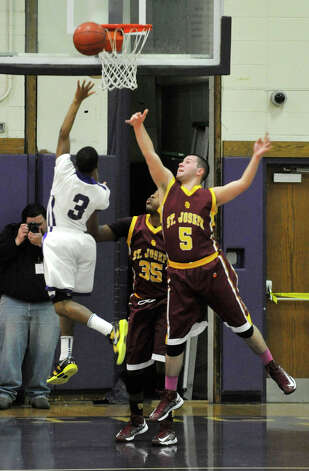 Westhill's C.J. Donaldson shoots over the leaping Jonathan Dzurenda, of St. Joseph, during their game at Westhill High School in Stamford on Monday, Feb. 18, 2013. St. Joseph won, 63-61. Photo: Jason Rearick / The News-Times