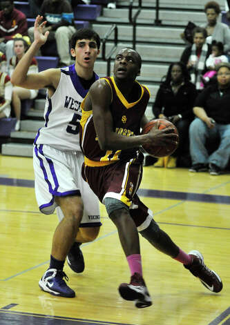 St. Joseph's Quincy McKnight drives the ball to the hoop past Westhill's Evan Skoparantzas during their game at Westhill High School in Stamford on Monday, Feb. 18, 2013. St. Joseph won, 63-61. Photo: Jason Rearick / The News-Times