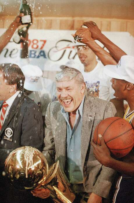 FILE - In this June 15, 1987 file photo, Los Angeles Lakers owner Jerry Buss gets doused with champagne from members of his team as he holds the NBA Championship trophy after the Lakers defeated the Boston Celtics 106-93 to win the NBA Championship four games to two in Inglewood, Calif. Buss, the Lakers' playboy owner who shepherded the NBA franchise to 10 championships, has died. He was 80. Bob Steiner, an assistant to Buss, confirmed Monday, Feb. 18, 2013  that Buss had died in Los Angeles. Further details were not available. (AP Photo/Lennox Mclendon, File) Photo: LENNOX MCLENDON, STF / AP