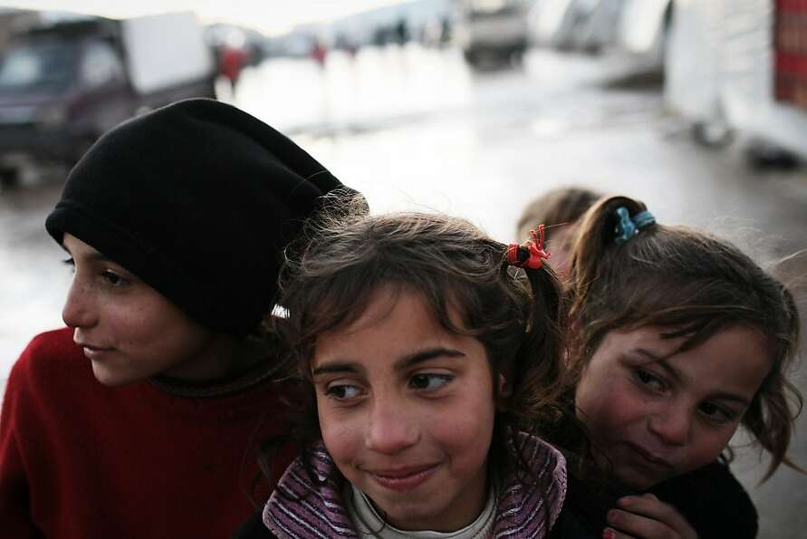 Three young displaced Syrian girls are seen in the Azaz camp for displaced people north of Aleppo pr