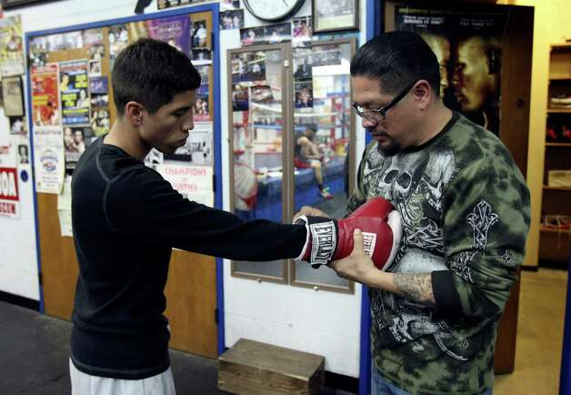 Johnny Garcia, 45, helps his son Nicholas, 19 with his gloves at Calderon Boys & Girls Club.  Nicholas will compete in next week's Golden Gloves competition. Photo: Helen L. Montoya, San Antonio Express-News / ©2013 San Antonio Express-News