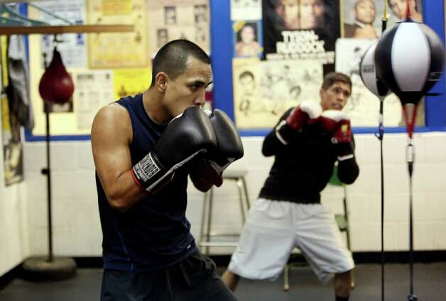 James Juarez, left,  and Nicholas Garcia, train at the Calderon Boys & Girls Club where they are trained by their fathers.  The pair will compete in next week's Golden Gloves competition. Photo: Helen L. Montoya, San Antonio Express-News / ©2013 San Antonio Express-News