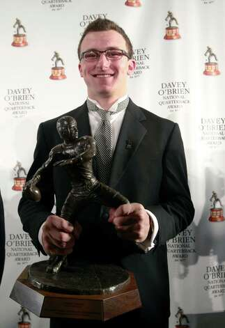 Texas A&M quarterback Johnny Manziel, winner of the Davey O'Brien Award, poses with the trophy during a news conference at the Fort Worth Club, Monday, Feb. 18, 2013 in Fort Worth, Texas.  The award is given to the nation's top NCAA college football quarterback.  (AP Photo/The Fort Worth Star-Telegram, Rodger Mallison) Photo: Rodger Mallison, Associated Press / Fort Worth Star-Telegram