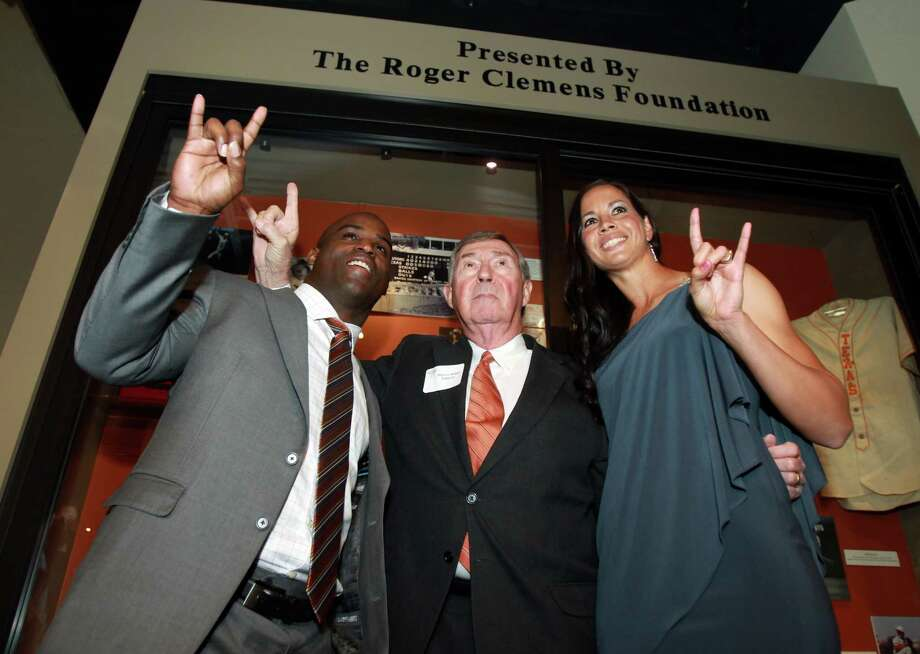 "From left, former Texas football player and Heisman Trophy winner Ricky Williams, Texas athletic director DeLoss Dodds and former Texas softball pitcher Cat Osterman give the ""Hook 'em Horns"" hand sign at a reception before the induction for the 2013 class of the Texas Sports Hall of Fame, Monday, Feb. 18, 2013, in Waco, Texas. Photo: Jerry Larson, Associated Press / The Waco Tribune-Herald"