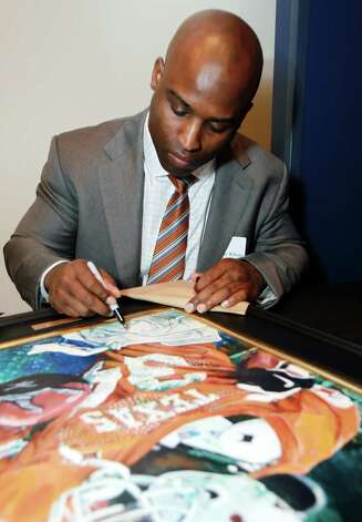 Former Texas football player and Heisman trophy winner Ricky Williams signs a poster at a reception before the induction for the 2013 class of the Texas Sports Hall of Fame, Monday, Feb. 18, 2013, in Waco, Texas. Photo: Jerry Larson, Associated Press / Waco Tribune Herald