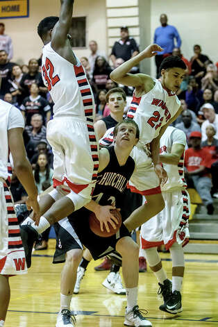 Churchill's Brian Herring (center) waits under the basket for a clear shot as Wagner's Tyler Collins (left) and Clint Lewis soar above him during the second half of their Class 5A bidistrict game at Clemens High School on Monday, Feb. 18, 2013.  Churchill beat the Thunderbirds 70-50. Photo: Marvin Pfeiffer, San Antonio Express-News / Express-News 2013