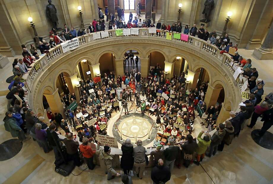 An overflow crowd gathered in the State Capitol Rotunda for a rally calling for an end to gun violence Monday, Feb. 18, 2013, in St. Paul, Minn. (AP Photo/Jim Mone) Photo: Jim Mone, Associated Press
