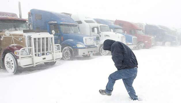 Wes Bevans, a truck driver from Northern California, walks to his truck at the Flying J Travel Plaza in Grand Forks, N.D., Monday, Feb. 18, 2013, during a blizzard. Dozens of semi trucks were forced to wait out the storm as Interstate 29 from Grand Forks to the Canadian border closed. (AP Photo/Grand Forks Herald, Eric Hylden) Photo: Eric Hylden, Associated Press