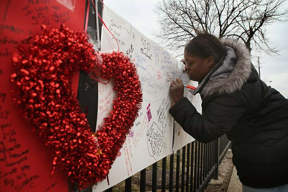 Robin Pettus signs a memorial to her eighteen-year-old cousin Frances Colon near the spot where she was murdered on February 18, 2013 in Chicago, Illinois. Colon, who was shot February 15th while walking by a neighborhood play lot, was the 51st person murdered in Chicago in 2013. She was the third student from Roberto Clemente High School, a Westside school with less than 800 students, to be murdered in the past three months.  (Photo by Scott Olson/Getty Images) Photo: Scott Olson, Getty Images