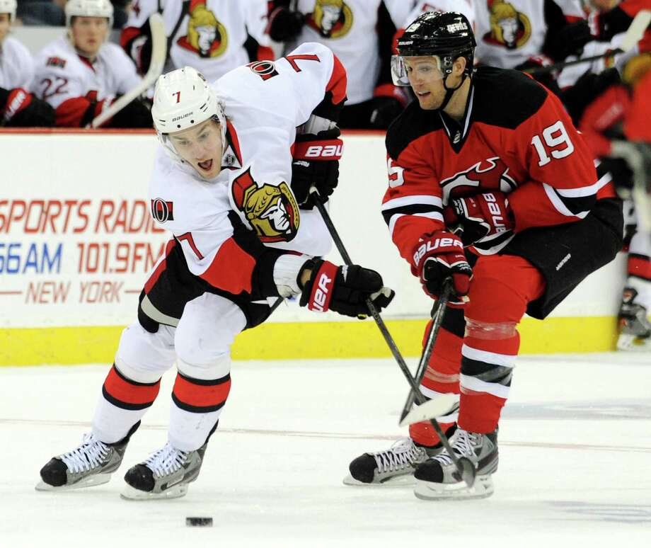 Ottawa Senators' Kyle Turris, left, and New Jersey Devils' Travis Zajac chase after the puck during the first period of an NHL hockey game Monday, Feb. 18, 2013, in Newark, N.J. The Senators won 2-1 in a shootout. (AP Photo/Bill Kostroun) Photo: Bill Kostroun