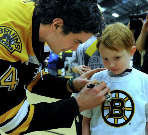 Adam McQuaid of the Boston Bruins hockey team signs an autograph for Martin Dunn, 5, of Sandy Hook. The Bruins held hockey clinics for Newtown kids at the Newtown Youth Academy, Monday, Feb. 18, 2013. Photo: Carol Kaliff / The News-Times