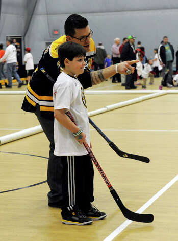 Bruin player Andrew Ference works with kids at a hockey clinic Monday. The Boston Bruins hockey team held hockey clinics for Newtown kids at the Newtown Youth Academy, Monday, Feb. 18, 2013. Photo: Carol Kaliff / The News-Times