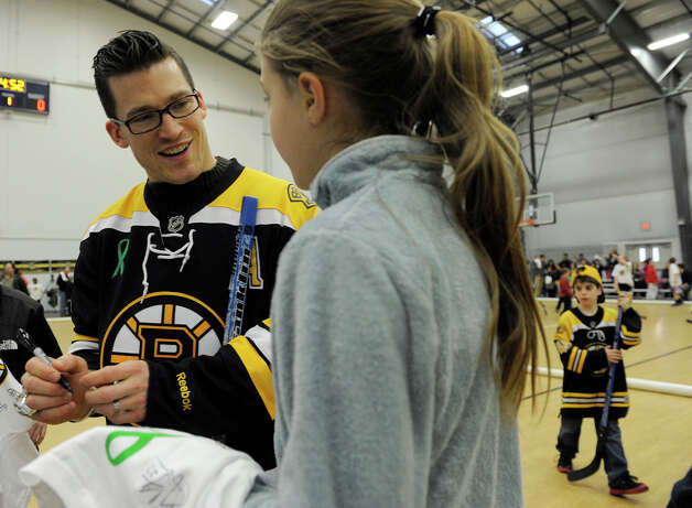 Boston Bruin player Andrew Ference signs an autograph Monday. The Boston Bruins hockey team held hockey clinics for Newtown kids at the Newtown Youth Academy, Monday, Feb. 18, 2013. Photo: Carol Kaliff / The News-Times