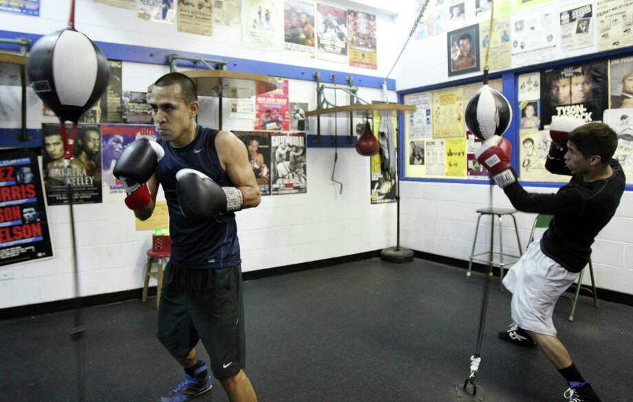 James Juarez (left) and Nicholas Garcia train at Calderon Boys & Girls Club, where their fathers help them. Like the fathers years ago, they are friends and training partners. Photo: Helen L. Montoya / San Antonio Express-News