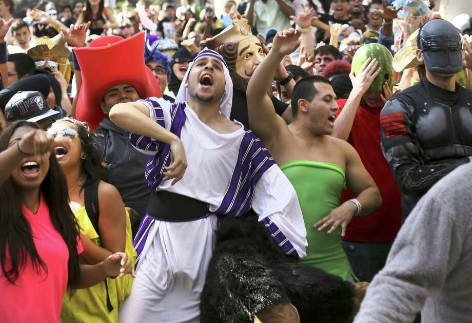 "Mostafa Altameemi (in white) and Bennie Luza (in green) join with hundreds of other University of Texas at San Antonio students for a ""Harlem Shake"" at the Sombrilla, the main campus' covered plaza. Photo: Bob Owen / San Antonio Express-News"