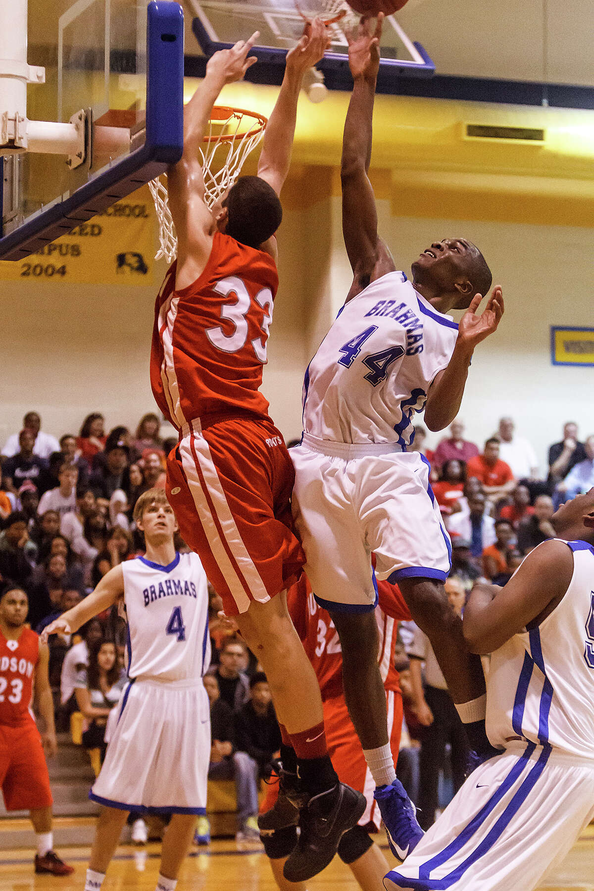 MacArthur's Marco McKee (right) blocks a shot by Judson's David Wacker during the second half of their Class 5A bidistrict game at Clemens High School on Monday, Feb. 18, 2013. Judson won the game 49-45.