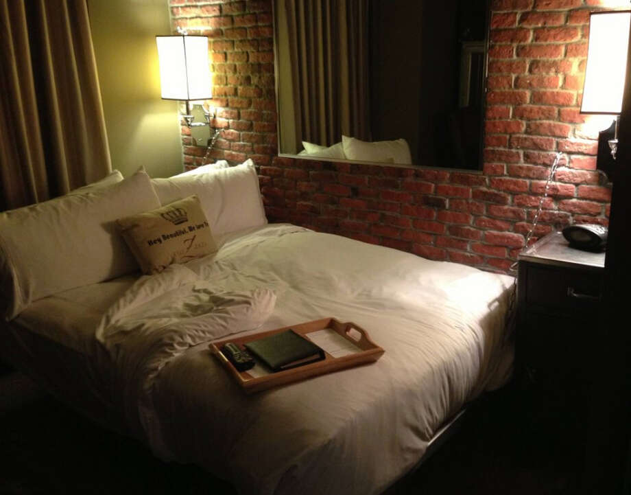 "The bed is ""chained"" to the brick wall in Room 322 at Hotel Zaza. Photo: Imgur.com"