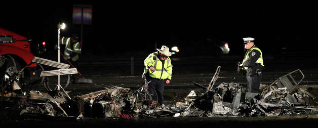 Officials examine the remnants of a tanker truck crash on Interstate 10 westbound near Ralph Fair Road that took place before 3 a.m. Tuesday, Feb. 19, 2013. The driver of the truck died and traffic on the interstate was closed in both directions for hours and diverted to the highway's feeder roads. Photo: John Davenport/Express-News / ©San Antonio Express-News/Photo Can Be Sold to the Public