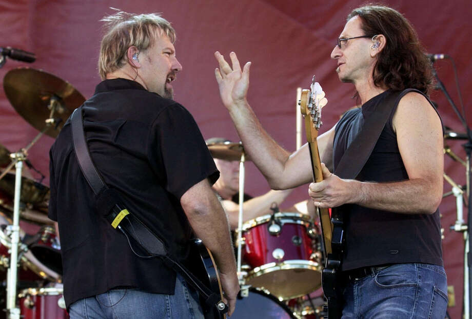 Alex Lifeson, left, and Geddy Lee of Rush perform during the concert for SARS relief at Downsview Park in Toronto, Canada Wednesday July 30, 2003.  Tens of thousands of sun-drenched revelers gathered Wednesday for a star-studded outdoor bash _ headlined by the Rolling Stones _ aimed at showing Toronto is free of SARS and ready to rock. Photo: AARON HARRIS, AP / CP