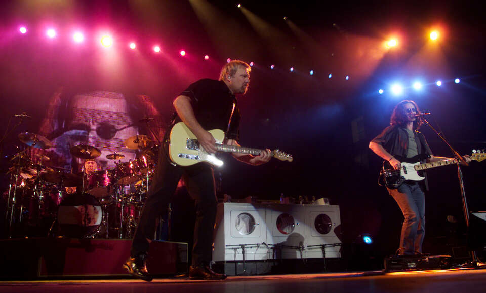 Rush band members Geddy Lee, right, Alex Lifeson, center, and drummer Neil Peart perform at the Blue