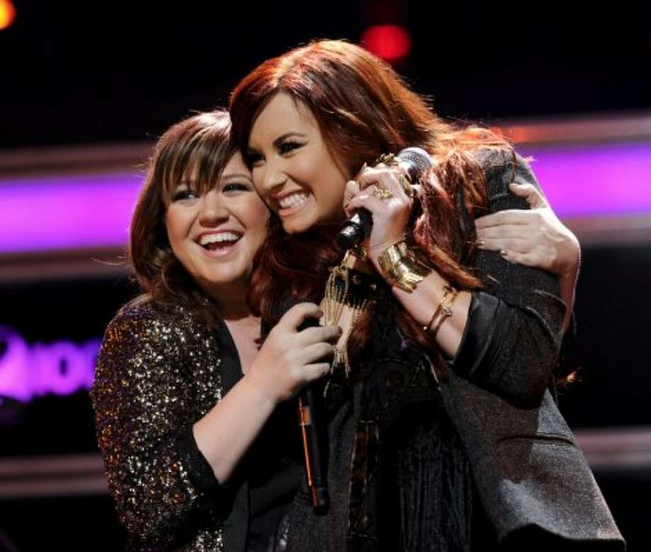 Singers Kelly Clarkson, left, and Demi Lovato perform together at Z100's Jingle Ball concert at Madison Square Garden on Friday, Dec. 9, 2011 in New York. (AP Photo/Evan Agostini)