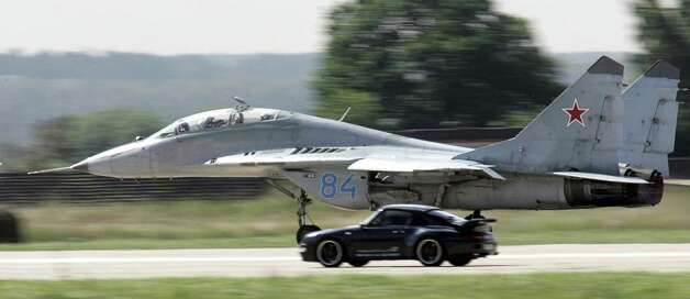 A Russian SU-27M competes with Porsche-911 car during the International festival of flight groups at Moscow International Air Show (MAKS) in Zhukovsky, in the Moscow region, 13 August 2004. Photo: YURI KADOBNOV, Getty Images / 2004 AFP