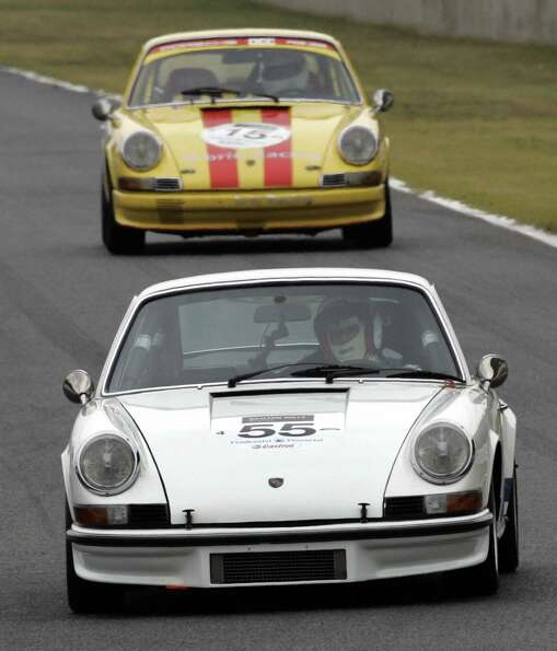 Junichi Yamano drives his 1973 Porsche 911 to lead a 1971 Porsche 911T during the round one of the c