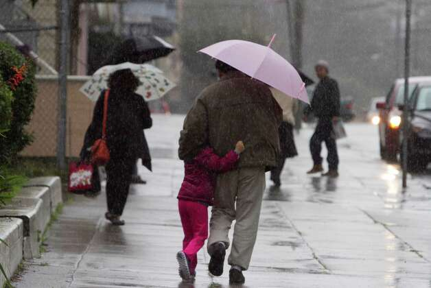 People huddle under umbrellas during a downpour in San Francisco on Tuesday morning. Photo: SF Gate / Douglas Zimmerman
