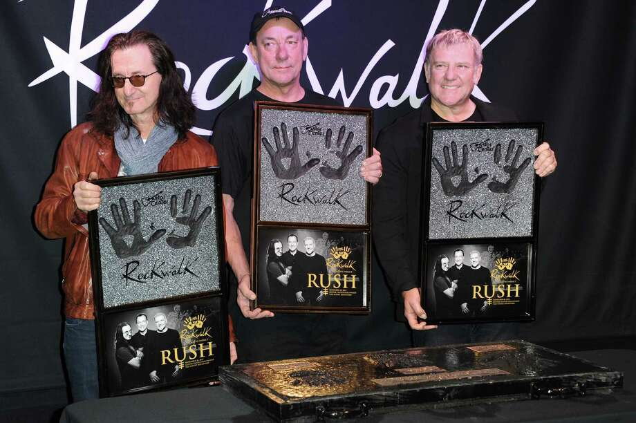 From left, Geddy Lee, Neil Peart, and Alex Lifeson attend the RockWalk induction of Rush at Guitar Center on Tuesday, Nov. 20, 2012, in Los Angeles. (Photo by Richard Shotwell/Invision/AP) Photo: Richard Shotwell / Invision