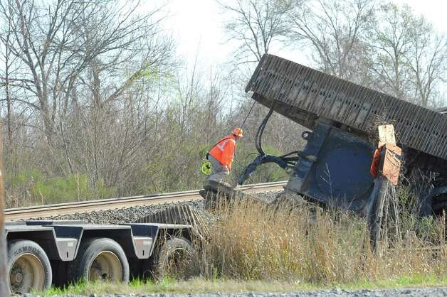An official looks over possible damage to the tracks. The Jefferson County Sheriff's Office and Union Pacific Railroad officials are at the scene of an accident on U.S. 90 in the area of China, where a train struck a loaded  18-wheeler. There is one reported death from the crash and the wreck happened at about 8 a.m. as the 18-wheeler with three construction workers were headed to a job site. The truck's trailer got stuck on the tracks, and two men tried to free the trailer while the third remained in the truck. The train struck the truck, killing one of the men outside the truck. The man inside the truck was taken by medical helicopter to Christus St. Elizabeth Hospital and is currently in critical condition. The third man was not injured.  Attempts to avoid debris in the road by passing vehicles resulted in a second wreck with two other vehicles. There were no injuries from that wreck.    Dave Ryan/The Enterprise