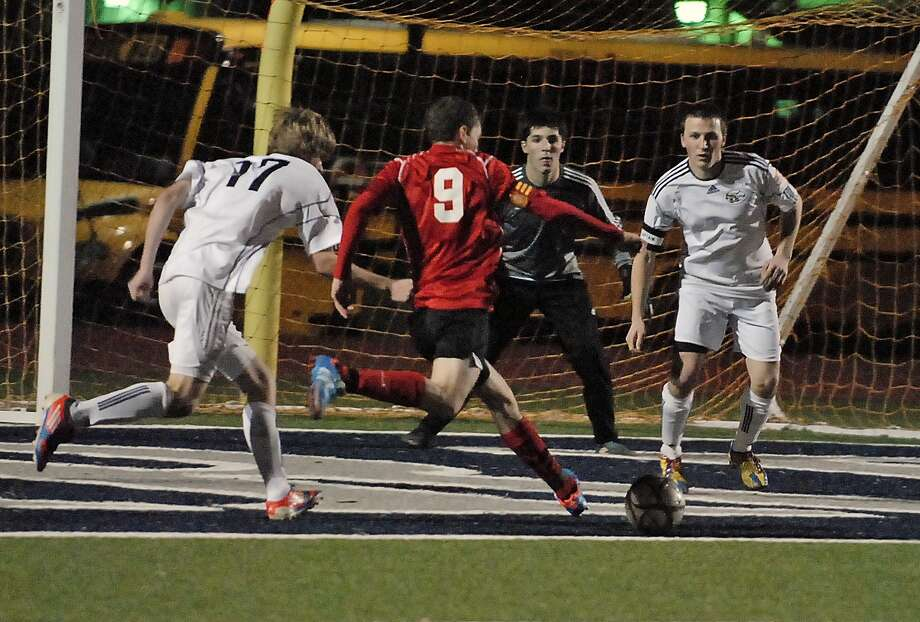Pope John XXIII senior forward Pedro Saiz (9) attacks the Second Baptist goal and scores with a kick between Will Brazelton (17) goalkeeper Derek Moore and defender Ian Giles (33). Photo:  Tony Bullard 2013, Freelance Photographer / © Tony Bullard & the Houston Chronicle