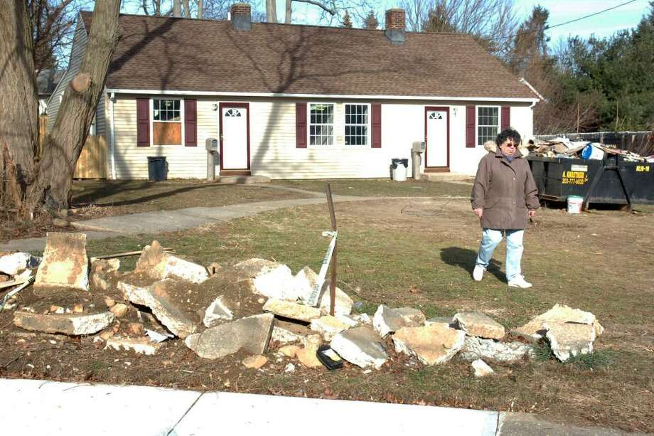 Anna Marie Perry walks in front of a duplex she owns at 75-79 High Ridge Dr. in Bridgeport, Conn. Dec. 30th, 2009. Perry says that she paid a contractor neary $20,000 to renovate the structure and install a paved driveway. Much of the renovation was never completed, and the driveway was never installed. Photo: Ned Gerard / Connecticut Post