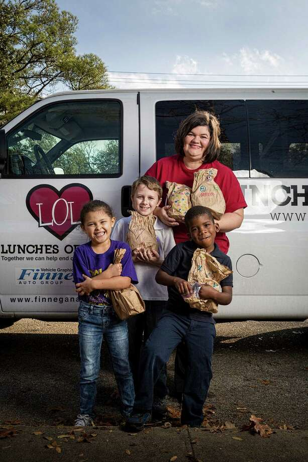 Jayda Pina, 5, from left, Hunter Bayless, 9, and Jonathan Carter, 6, hold lunches from Adriane Mathews Gray, creator of Lunches of Love. The nonprofit organization is committed to helping end childhood hunger. Photo: Michael Paulsen, Staff / © 2013 Houston Chronicle