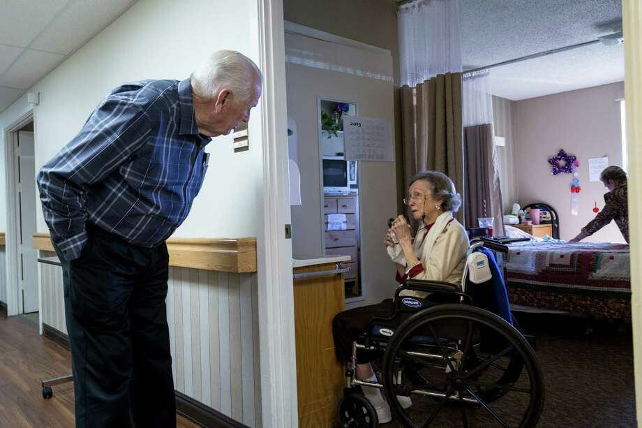 Clifford Layton talks with Christine Tucker as he makes his daily rounds visiting with residents of Windsong Village nursing home in Pearland. Photo: Michael Paulsen, Staff / © 2013 Houston Chronicle