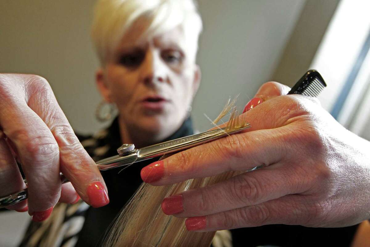 A former resident at the Women's Home, Cathy Bradley, 42, cuts the hair of a woman who is getting help at the residential treatment program.
