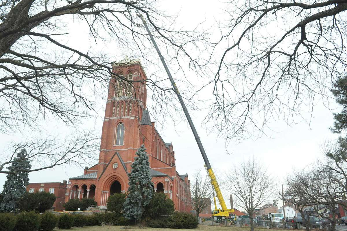 A large crane is set up alongside the former St. Patrick's Church as workers removed a large bell from the tower on Tuesday, Feb. 19, 2013, in Watervliet, NY. (Paul Buckowski / Times Union)