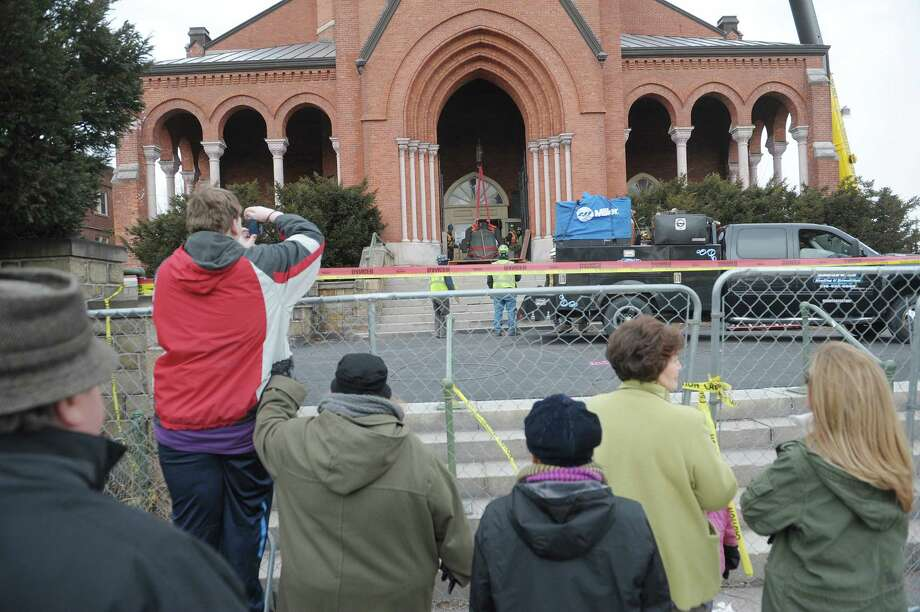 People gather at the security fence to watch and take photos as workers removed a large bell from the tower of the former St. Patrick's Church building on Tuesday, Feb. 19, 2013, in Watervliet, NY.  (Paul Buckowski / Times Union) Photo: Paul Buckowski / 00021226A