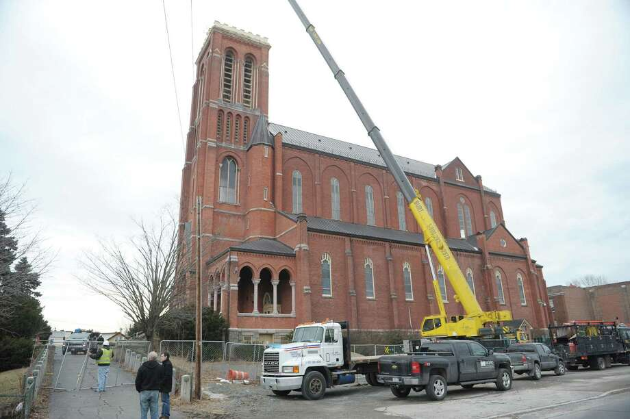A large crane is setup along side the structure  as workers removed a large bell from the tower of the former St. Patrick's Church building on Tuesday, Feb. 19, 2013 in Watervliet, NY.  (Paul Buckowski / Times Union) Photo: Paul Buckowski  / 00021226A