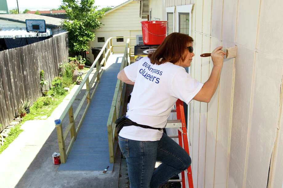 April Petty, a volunteer from BBVA Compass, paints a home, with a newly-built wheelchair ramp in the background, during a revitalization project in the East End neighborhood near Settegast Park Tuesday, April 24, 2012, in Houston.