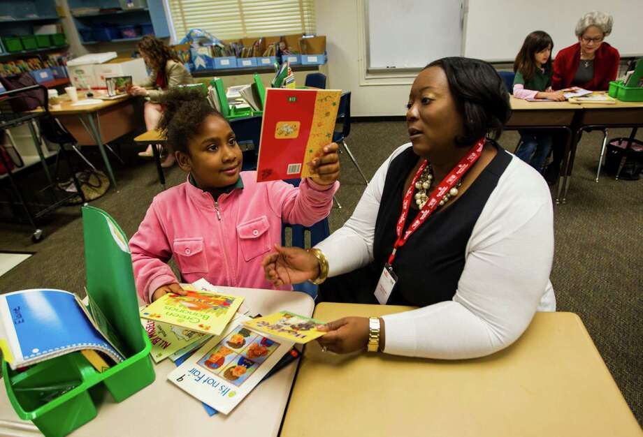 Volunteer Najah Callander helps second-grader Elaine Kennedy read during the United Way's Reading Together initiative at Spring Shadows Elementary School. Photo: Karen Warren, Staff / © 2013 Houston Chronicle